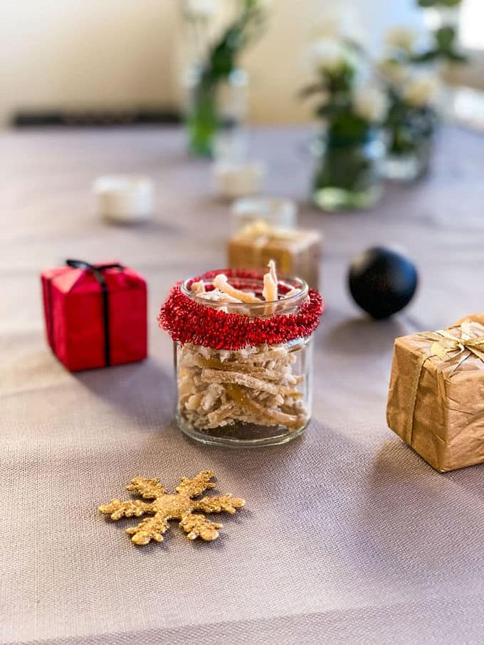 a jar of candied ginger with small wrapped gifts in the background