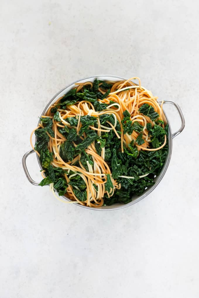a white colander with spaghetti and kale in it