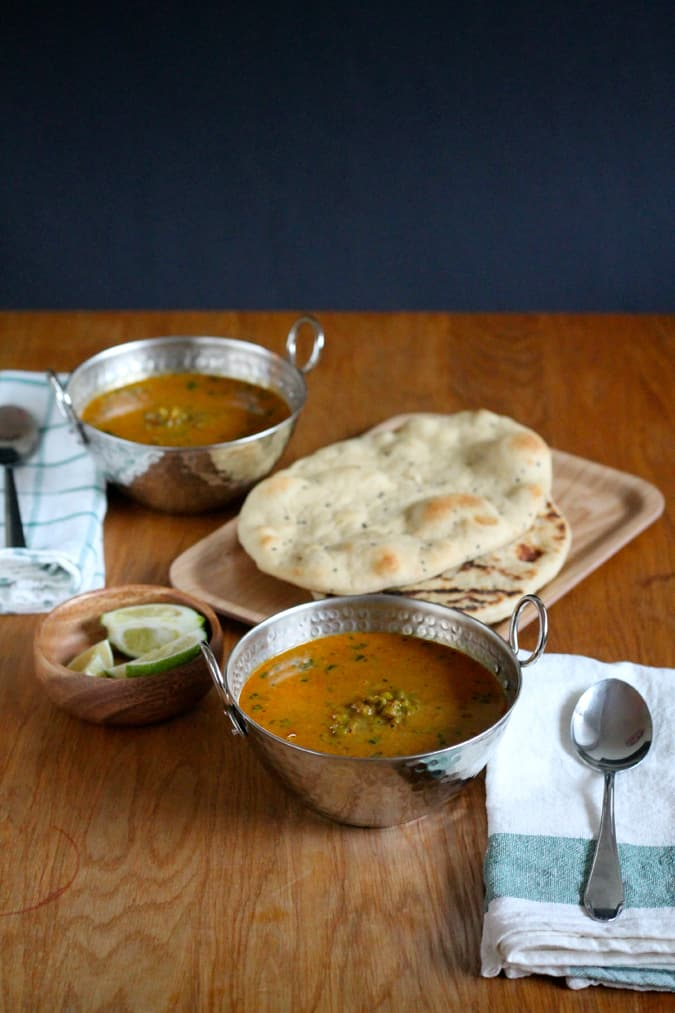 Two metal bowls of mung bean curry on a wooden table with a plate of naan in the background