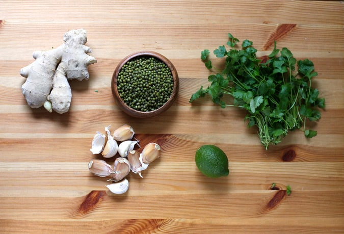 ginger, mung beans, garlic, lime, and cilantro on a wooden background