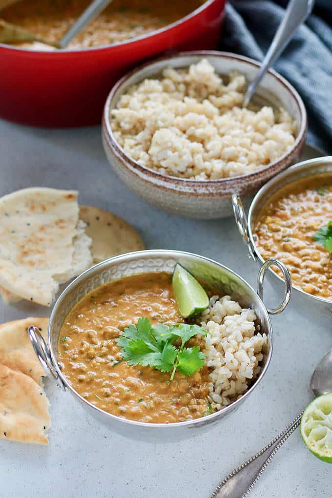 two bowls of mung bean and coconut curry with naan and brown rice in the background