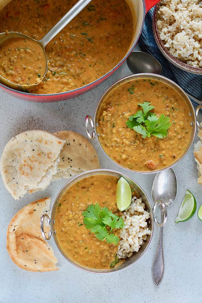 two bowls of mung bean curry on a grey background with naan bread and rice
