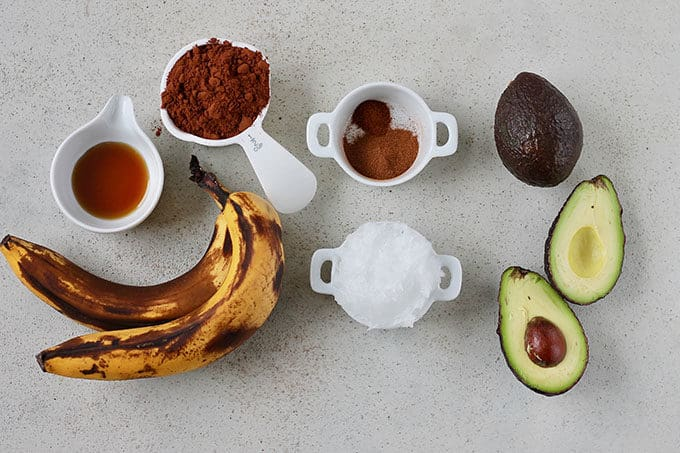 bananas, maple syrup, avocado, coconut oil, cocoa powder, spices, and avocados on a grey background