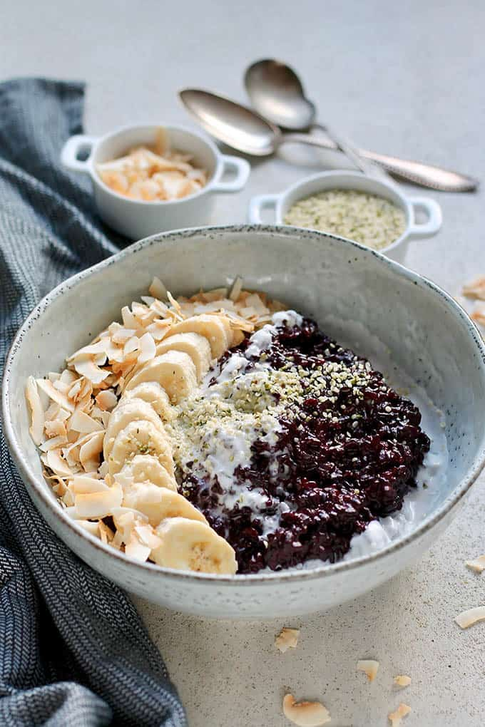 Indonesian black rice pudding in a large blue bowl topped with banana and coconut chips