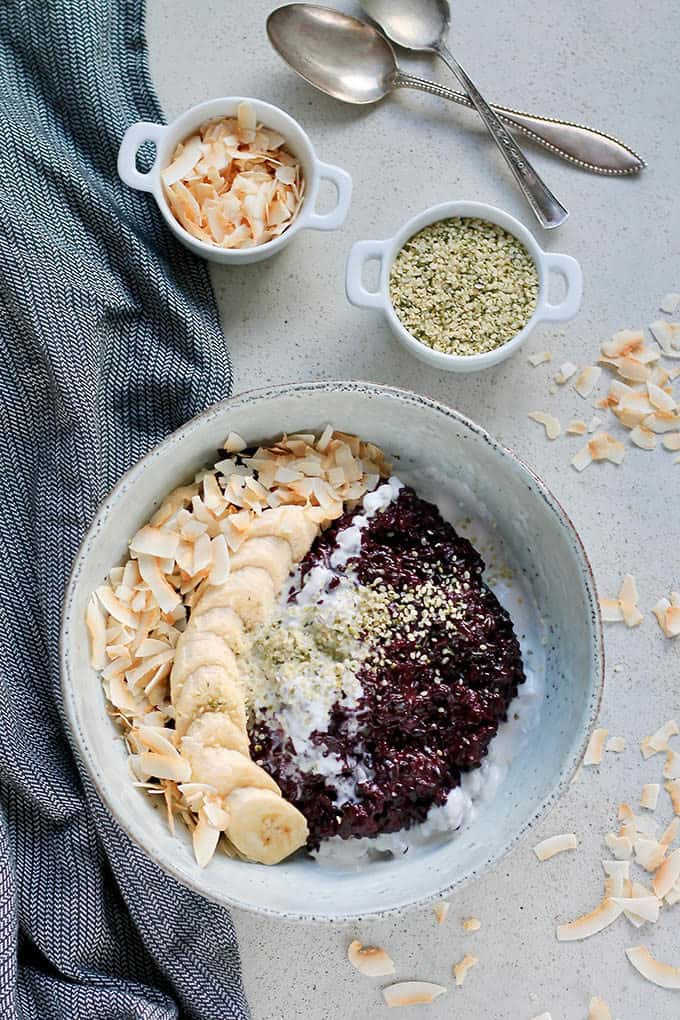 overhead photo of Indonesian black rice pudding in a blue bowl with hemp seeds and coconut chips
