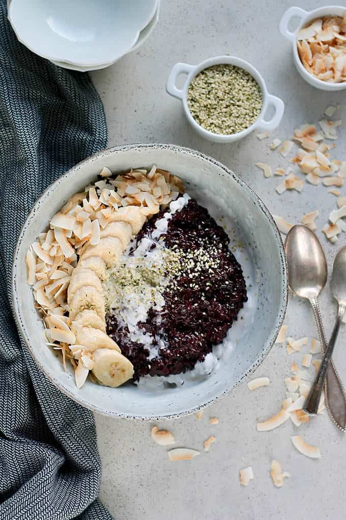 Indonesian black rice pudding on a grey surface with silver spoons to the side