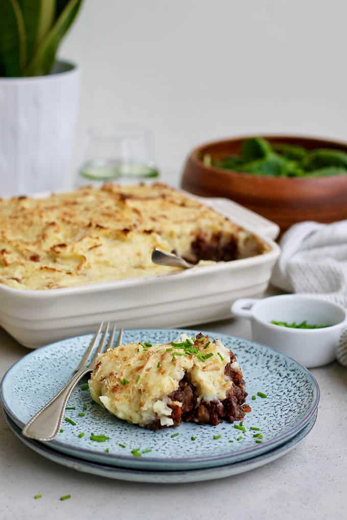 a plate of lentil shepherd's pie with a white casserole dish in the background