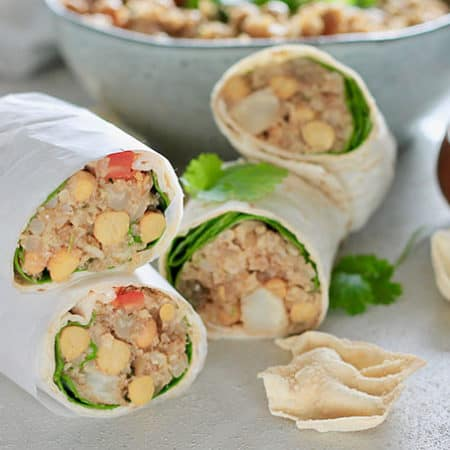 curried cauliflower chickpea wraps cut in half with a bowl of filling in the background