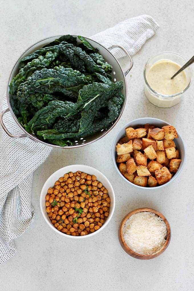 a collander full of kale, a bowl of crispy chickpeas, croutons, and vegetarian caesar dressing on a grey background