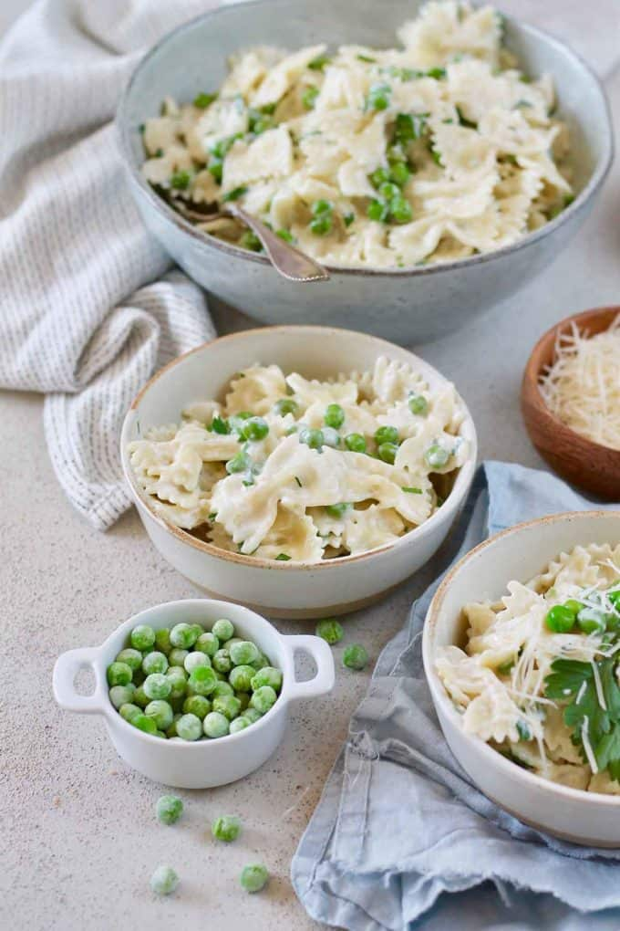 three bowls of bowtie pasta with peas on a grey surface