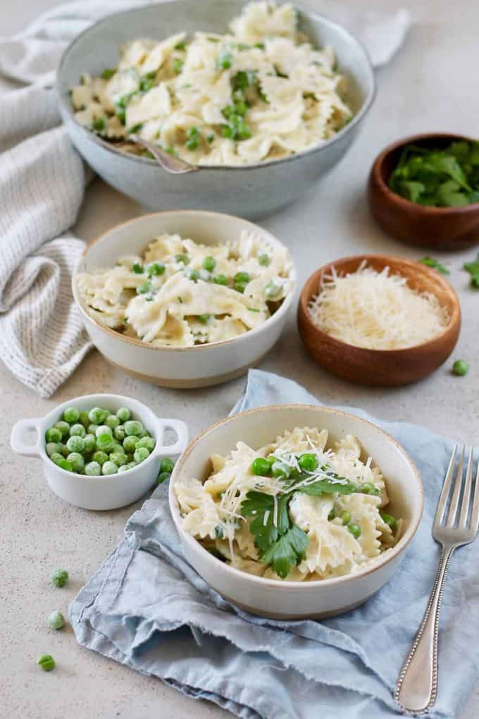 two bowls of pasta with peas on a grey background with a small bowl of frozen peas to the side