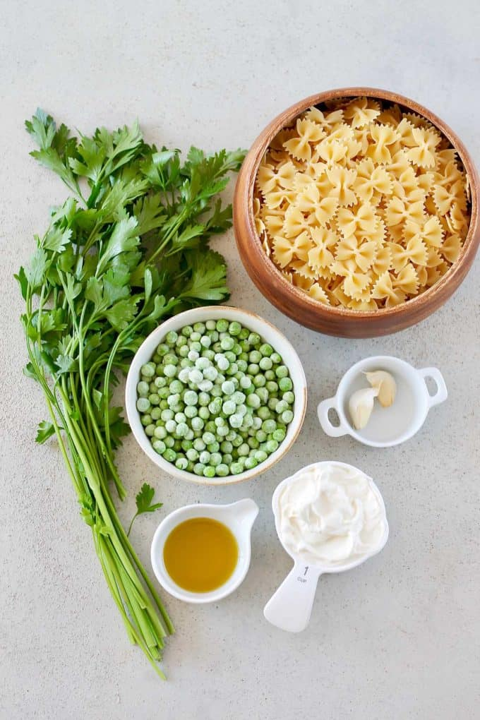 bowtie pasta, frozen peas, parsley, olive oil, yogurt, and garlic on a grey surface