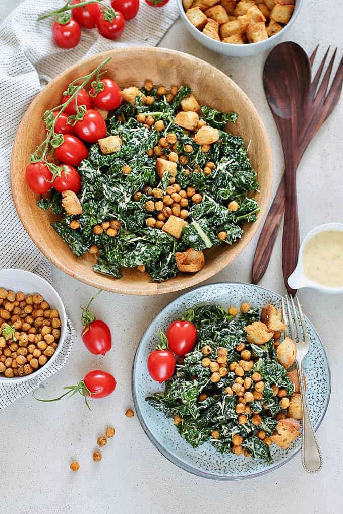 overhead photo of vegetarian caesar salad with kale, chickpeas, croutons, and tomatoes