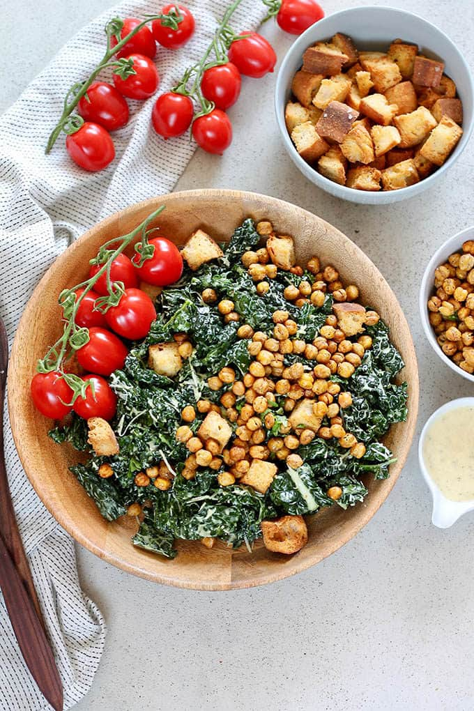 overhead photo of a kale caesar salad in a wooden salad bowl with cherry tomatoes on the side