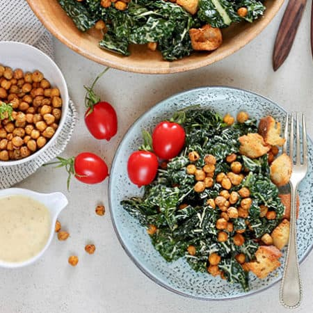 vegetarian caesar salad on a blue plate topped with chickpeas, croutons, and baby tomatoes