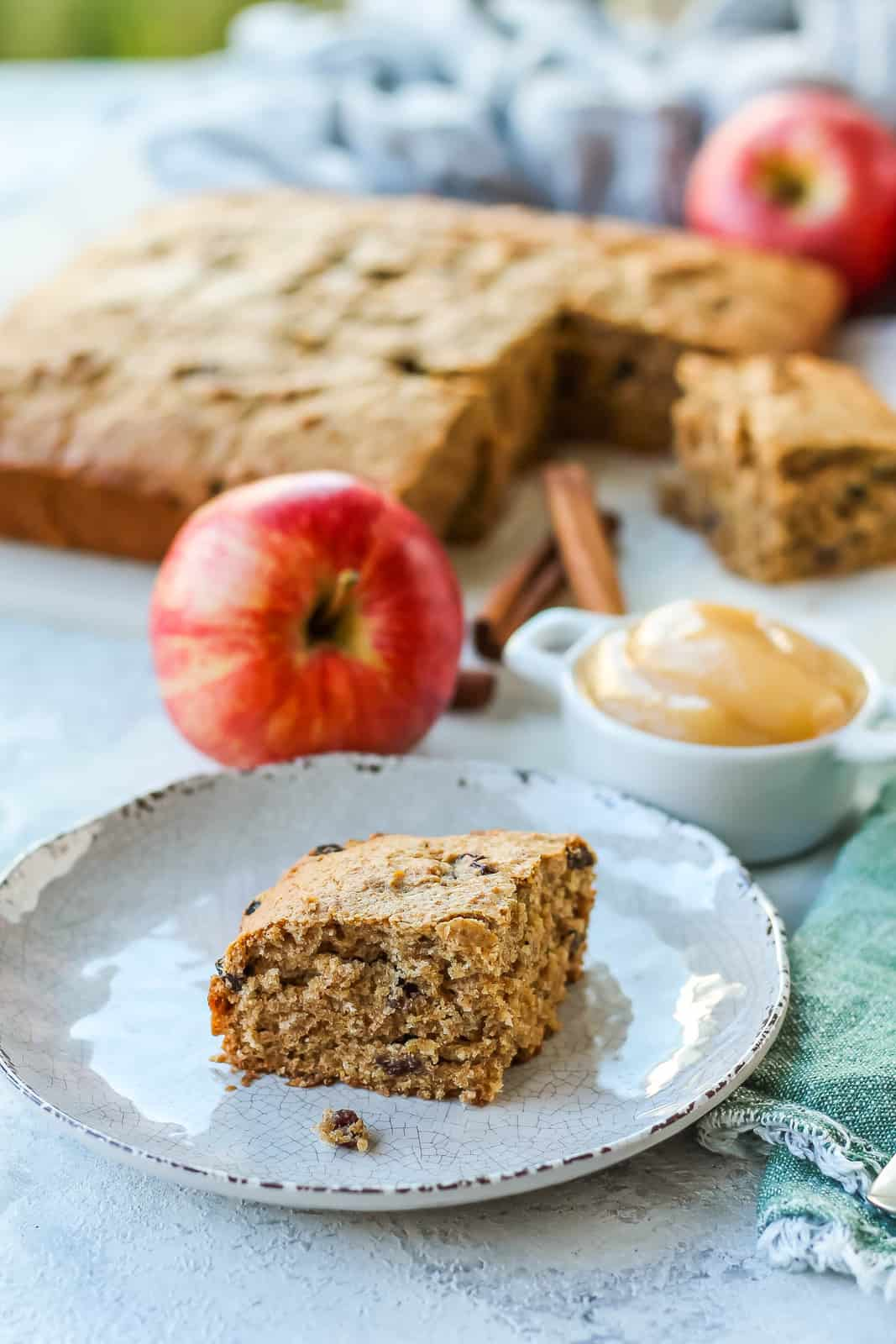 a square of applesauce snacking cake on a white plate with a tray of cake and some whole red apples in the background
