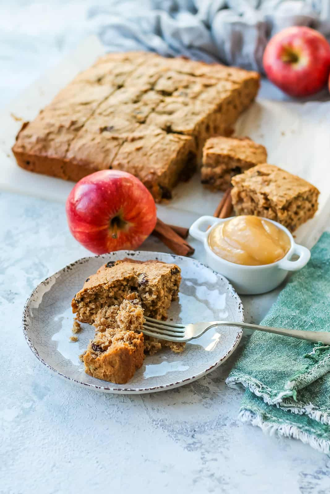 a square of healthy apple cake on a white plate with a silver fork breaking a piece off