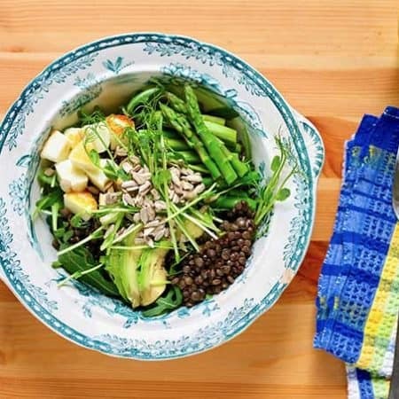 lentils, pan-fried halloumi, asparagus, and avocado in a white and blue patterned bowl