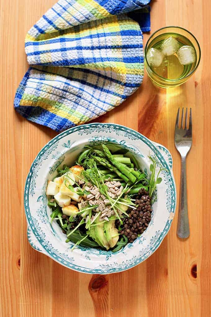 lentil bowl, blue napkin, glass of water with ice, and a fork on a wooden background.