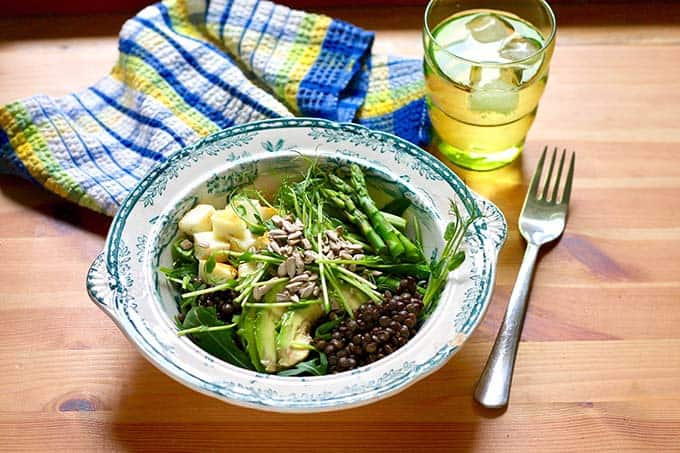 lentils topped with avocado, halloumi, pea shoots, and asparagus with a blue napkin and a glass of water in the background