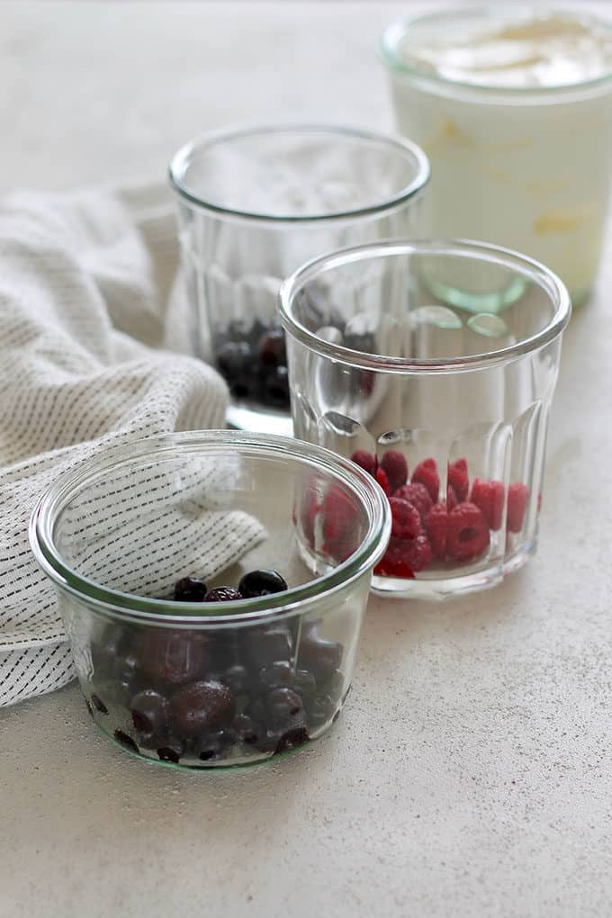 frozen berries in glass jars and a jar of yogurt on a grey background with a white tea towel to the side
