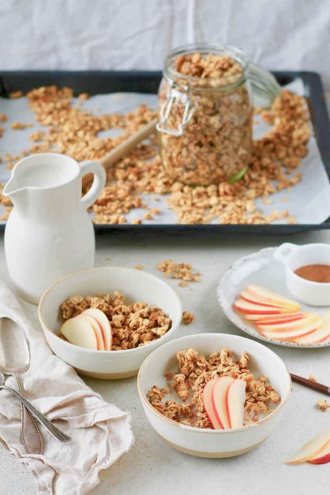 two bowls of apple granola with a jug of milk and a jar of granola in the background