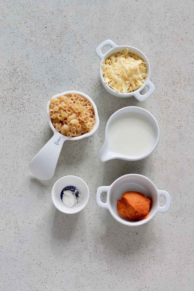 macaroni, cheese, pumpkin puree, milk, and cornstarch on a grey background