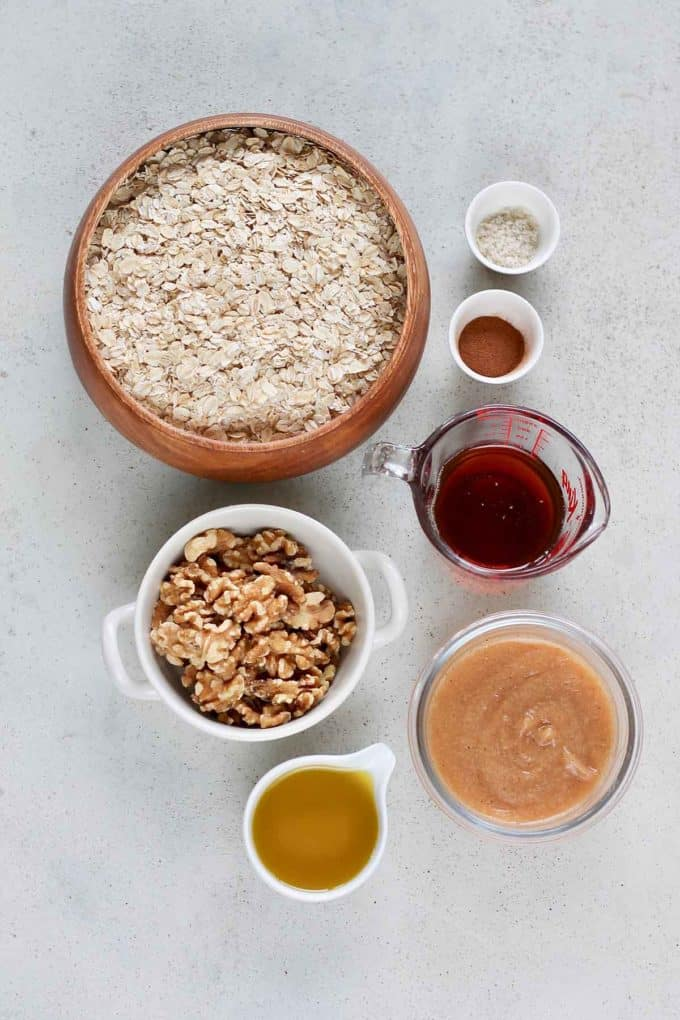 oats, walnuts, maple syrup, applesauce, oil, and cinnamon on a grey background