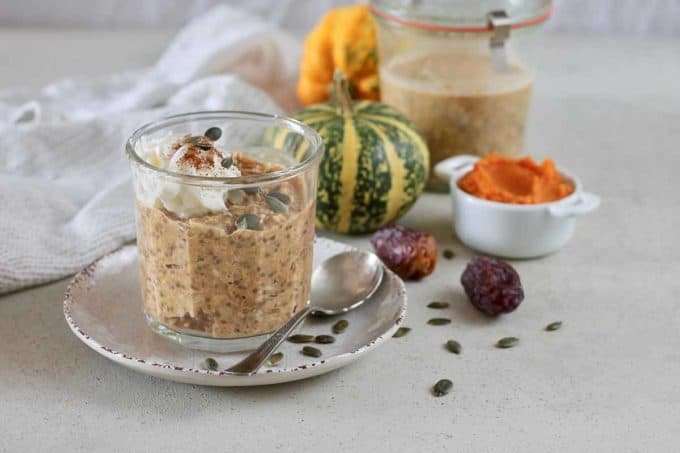 pumpkin overnight oats in a jar with a decorative pumpkin in the background