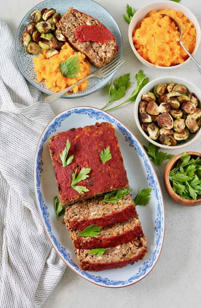 vegan meatloaf on a blue platter with roasted brussels sprouts and mashed squash to the side