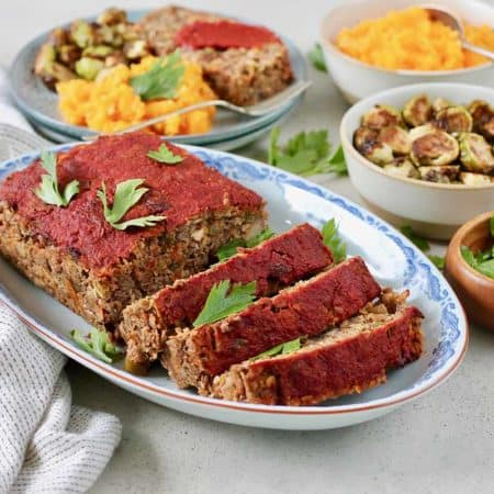 sliced vegan lentil loaf on a blue platter