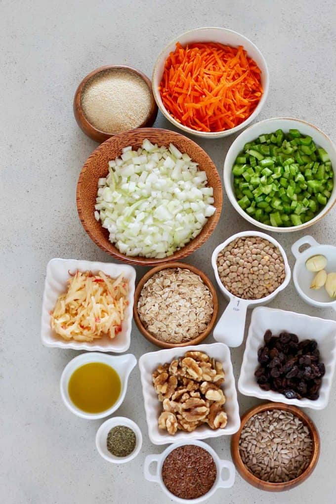 lentils, oats, bread crumbs, walnuts, sunflower seeds, grated carrot, diced celery, flax seeds, olive oil, diced onion, garlic, and thyme on a grey background
