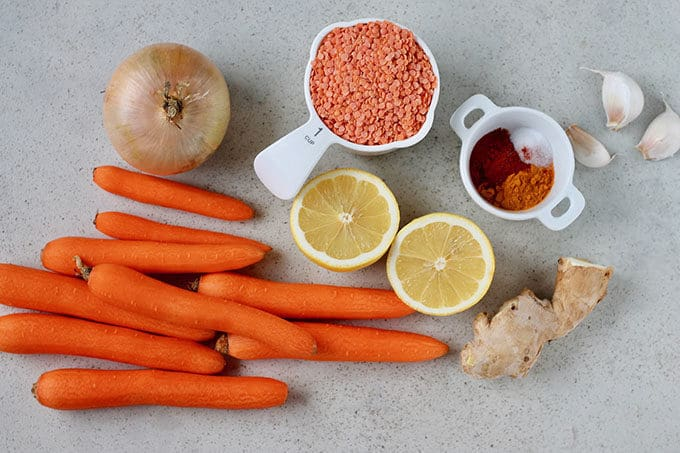 carrots, onion, lemon, red lentils, spices, ginger, and garlic on a grey background