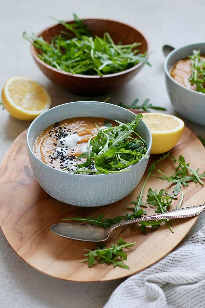 vegan carrot ginger soup in a blue bowl topped with arugula and lemon