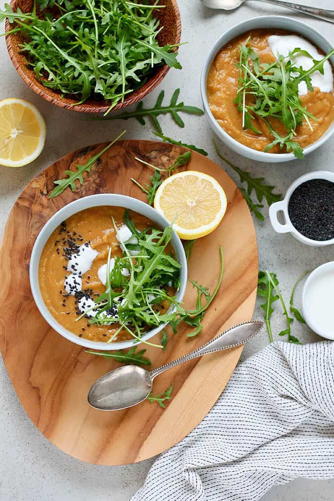 overhead photo of vegan carrot ginger soup in a blue bowl on a wooden platter