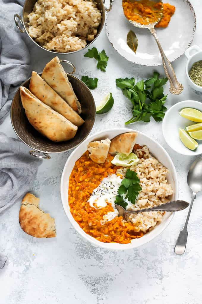 overhead photo of red lentil dal in a white bowl
