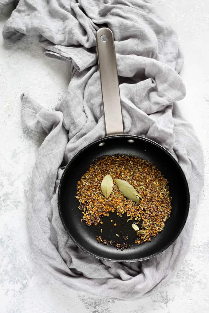 a mix of seeds being toasted in a frying pan on a grey gackground