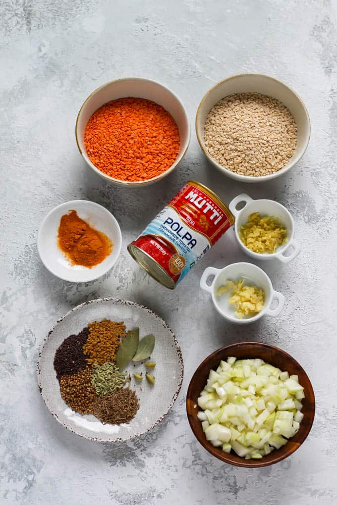 red lentils, urid dal, canned tomatoes, spices, ginger, garlic, and onions on a grey background