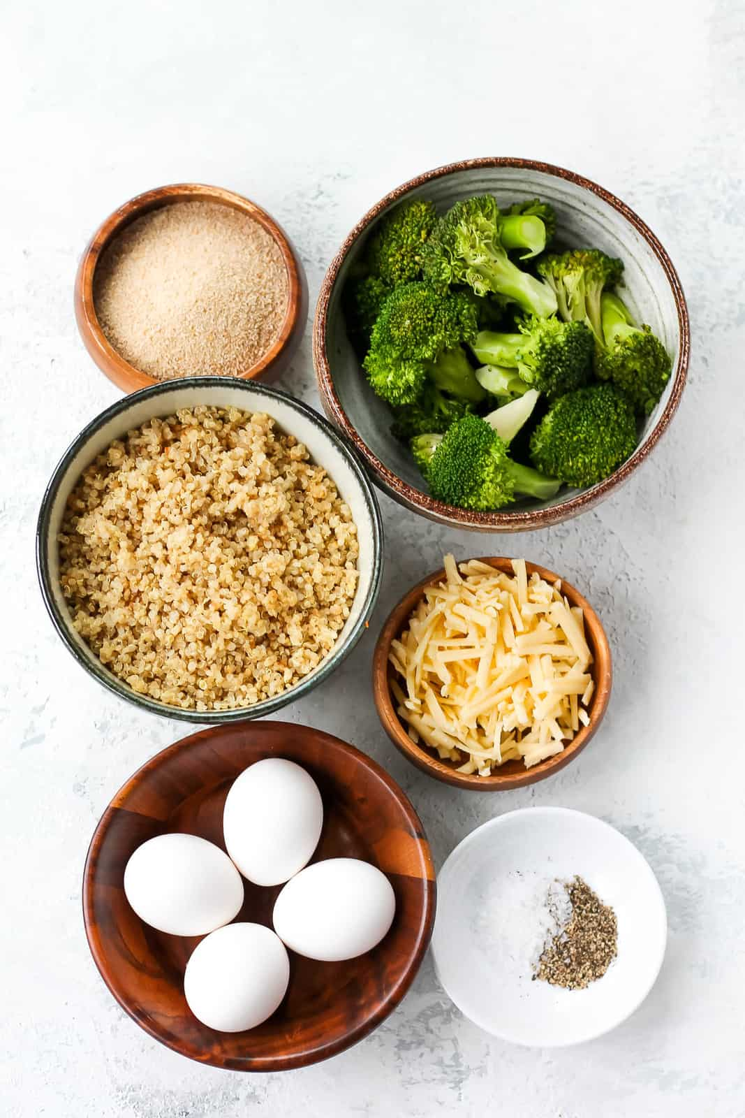 broccoli, quinoa, breadcrumbs, eggs, cheese, salt, and pepper on a grey background