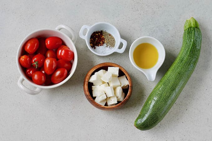 tomatoes, zucchini, halloumi, spices, and oil on a grey background