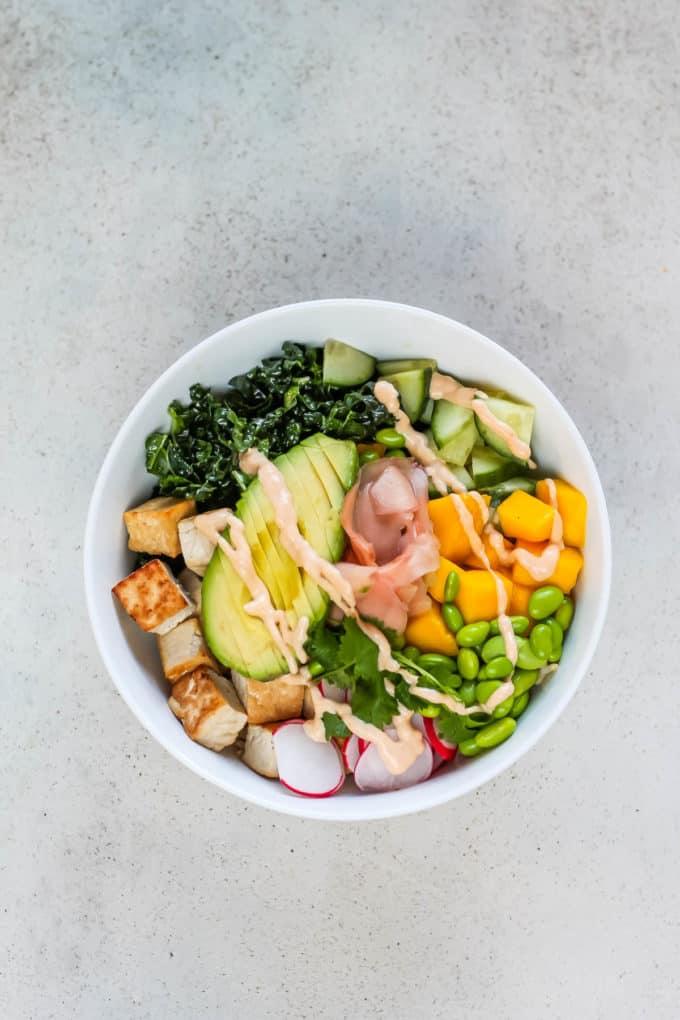 a vegan poke bowl on a grey background