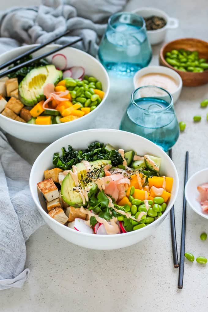 Vegan poké bowls in white bowls topped with avocado