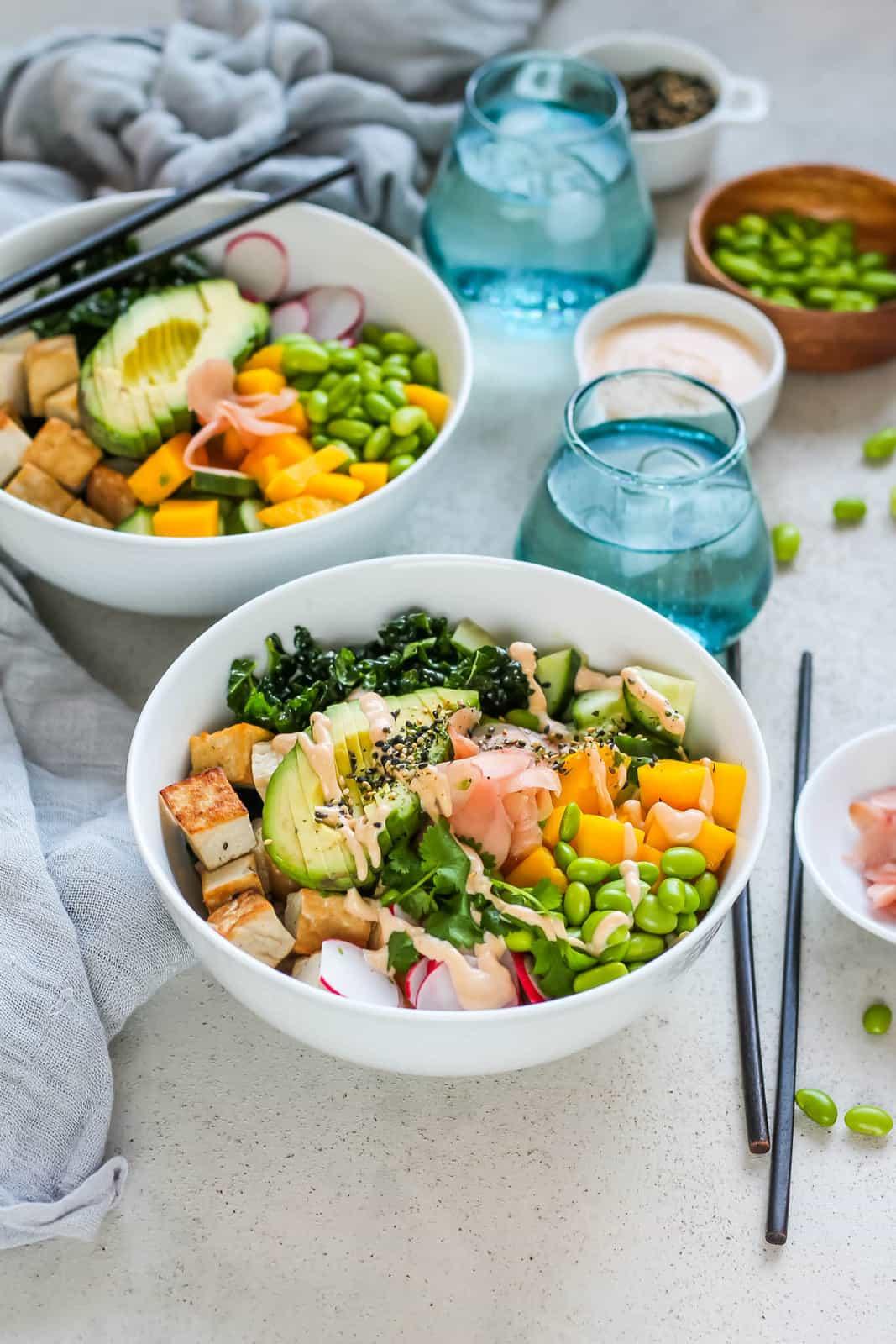 Vegan poké bowls in white bowls topped with avocado