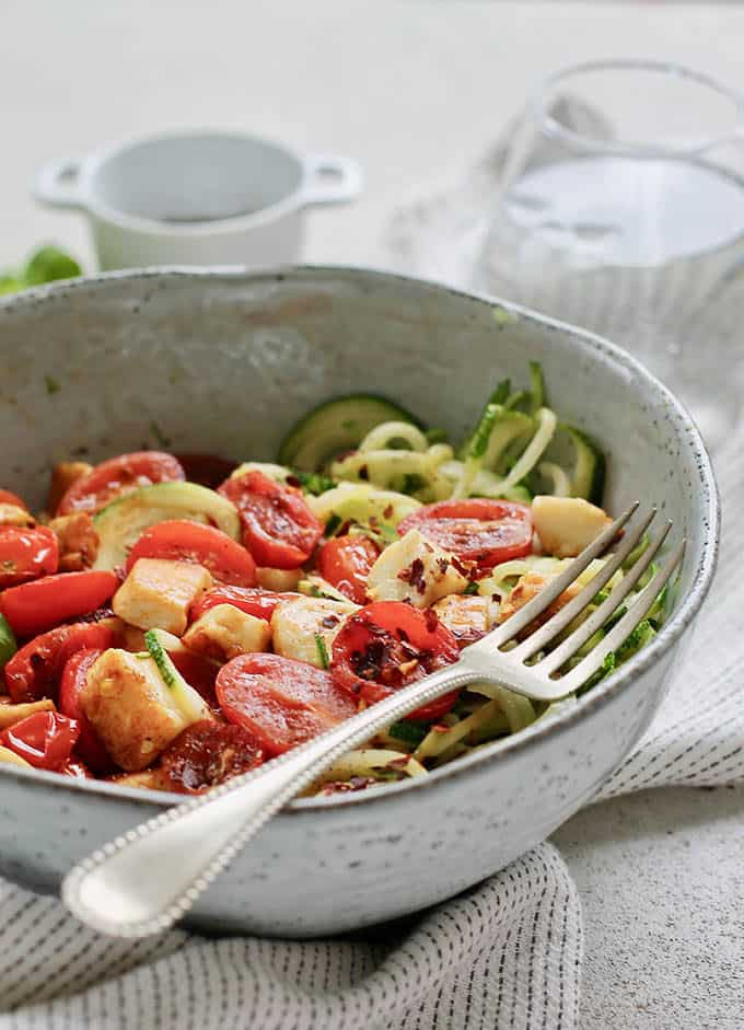 warm zucchini noodle salad in a blue bowl with a silver fork
