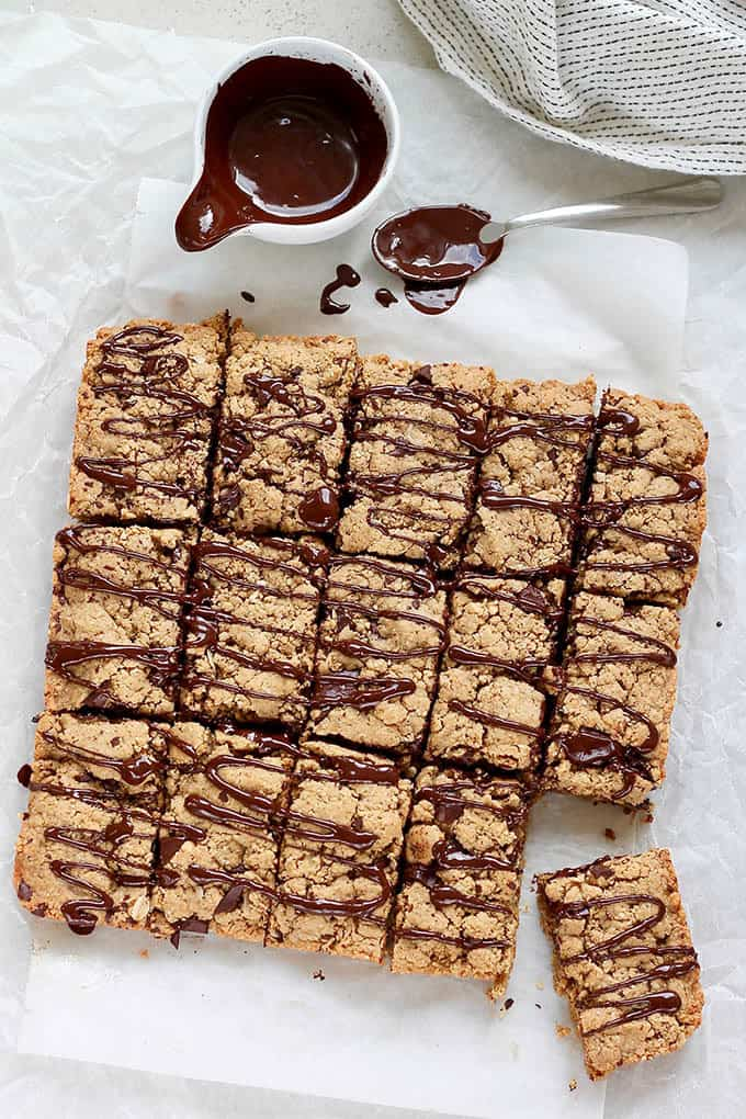 peanut butter oat bars drizzled with dark chocolate on a sheet of parchment paper