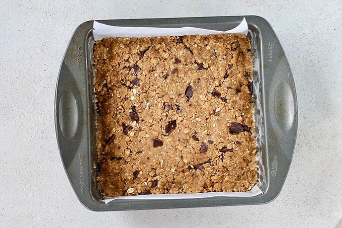 peanut butter oat bar dough pressed into a square baking pan