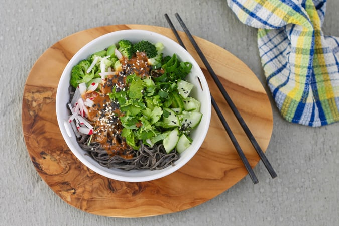 A white bowl with black bean noodles, vegetables, and sesame sauce on a wooden platter on a grey background