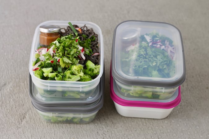 four lunch boxes with black bean noodles, vegetables, and a small jar of sauce tucked alongside.