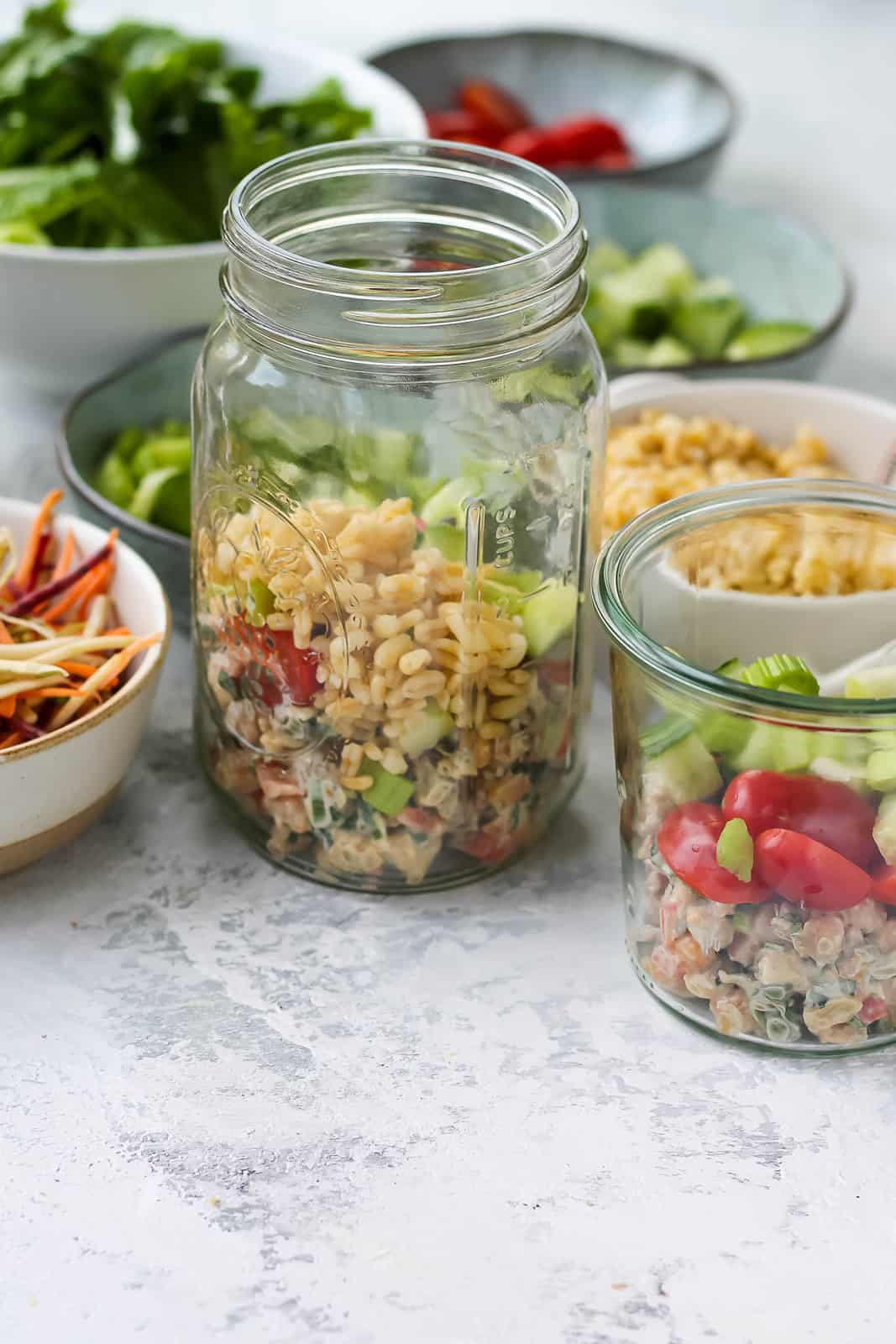 mason jars being filled with chickpea salad and vegetables on a grey background