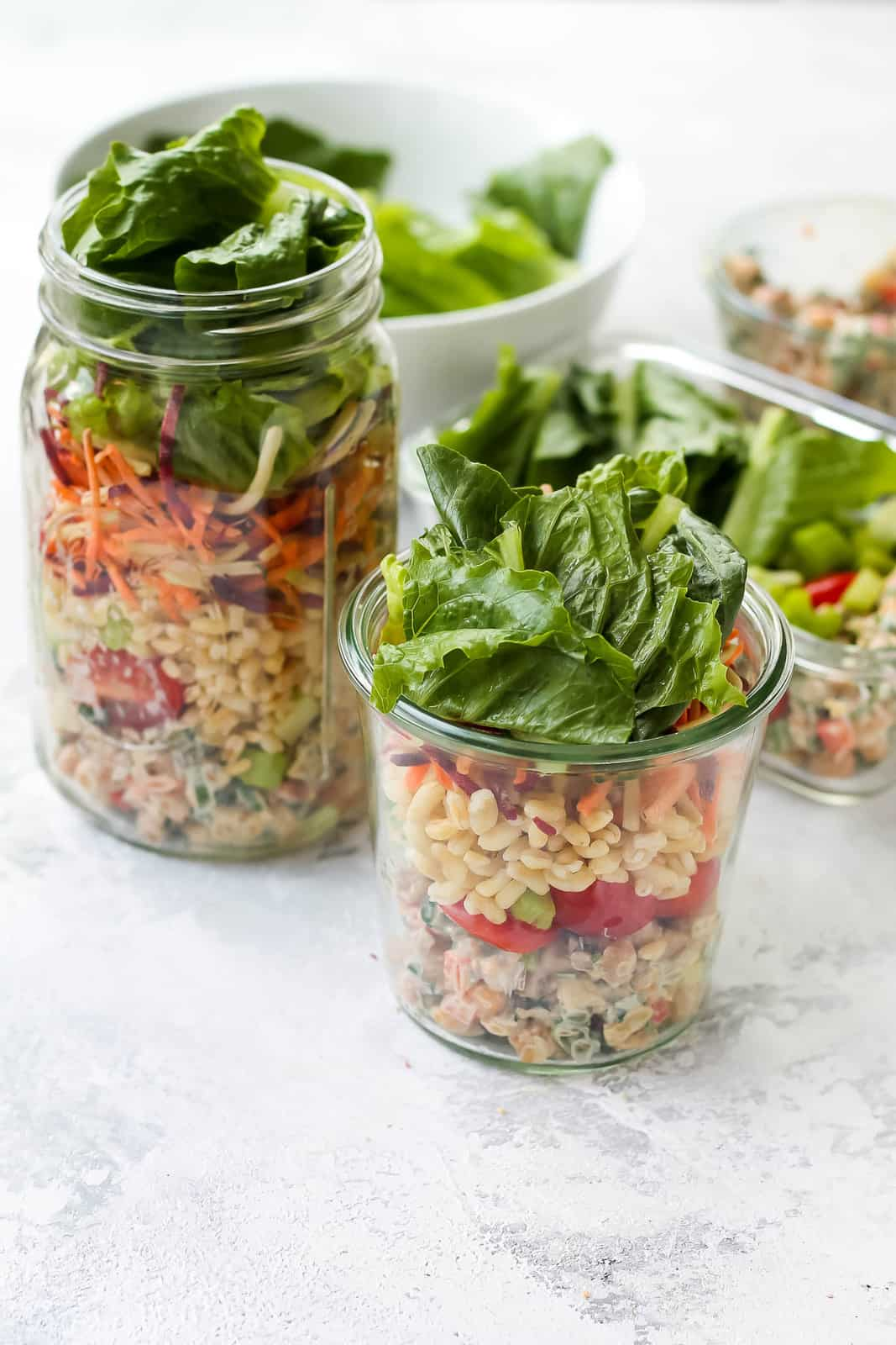 three mason jars filled with chickpea salad and topped with lettuce on a grey background